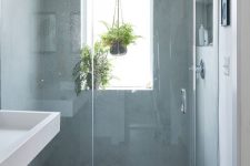 24 a neutral bathroom with a window with a frosted glass, pendant greenery, a grey tile floor looks ethereal and contemporary