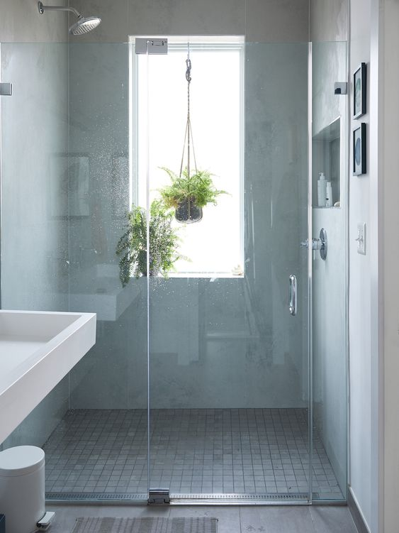 a neutral bathroom with a window with a frosted glass, pendant greenery, a grey tile floor looks ethereal and contemporary