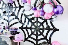 24 black glitter spider webs, marble white, pink and purple balloons and black balloon spiders are great for a bold Halloween party