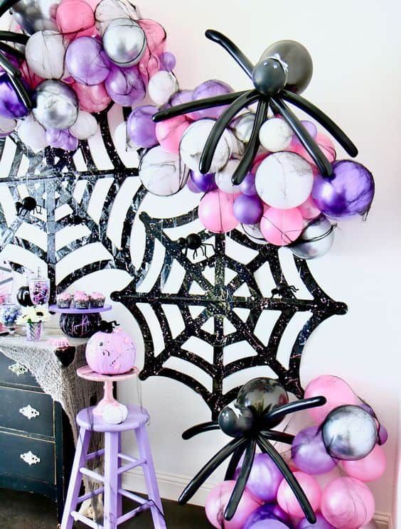 black glitter spider webs, marble white, pink and purple balloons and black balloon spiders are great for a bold Halloween party