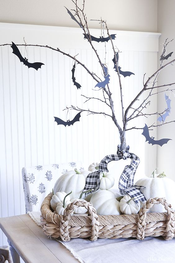 simple farmhouse Halloween decor with a basket with white pumpkins, branches with black bats attached to them