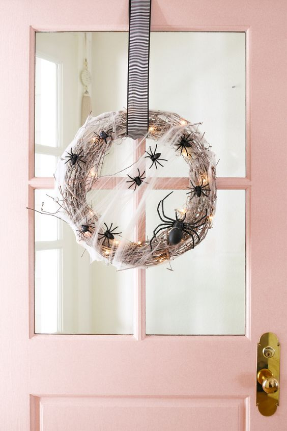 a lit up Halloween wreath with black spiders and a striped ribbon is a chic and cool idea for styling your front door and not only