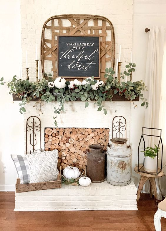 farmhouse fireplace styling with wood slices, churns, pumpkins, a tray with prined pillows, greenery and pumpkins on the mantel