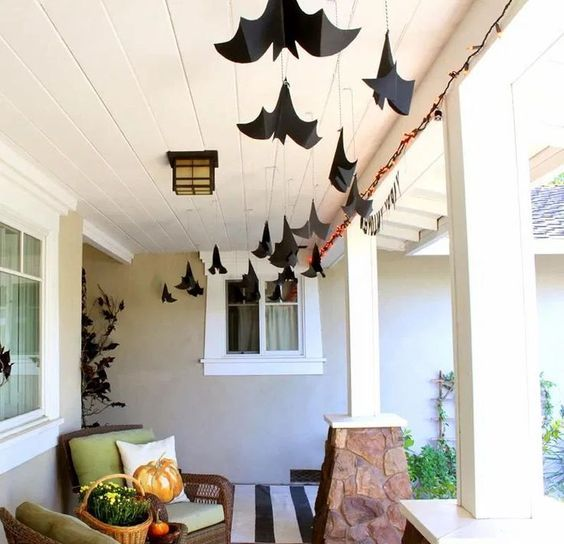 large black paper bats hanging down from the ceiling are great to style your porch for Halloween, back or front one