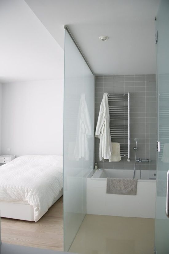 a neutral modern bedroom with a blue frosted glass space divider that separates a bathroom from the bedroom is a cool and fresh idea