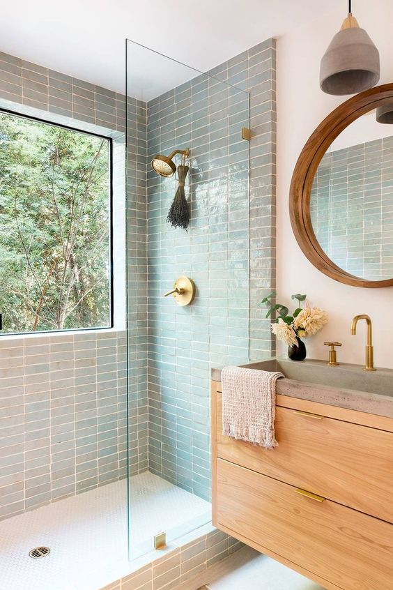 a welcoming mid-century modern bathroom with aqua tiles, stained furniture, a large window with a forest view right in the shower