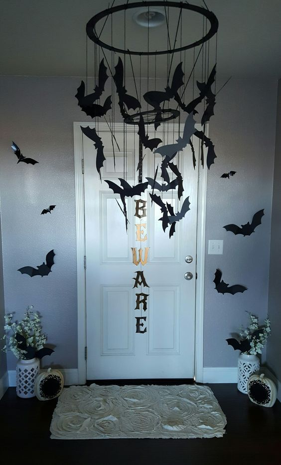 creative Halloween entryway with a black chandelier of black paper bats and some more bats on the walls is a cool idea