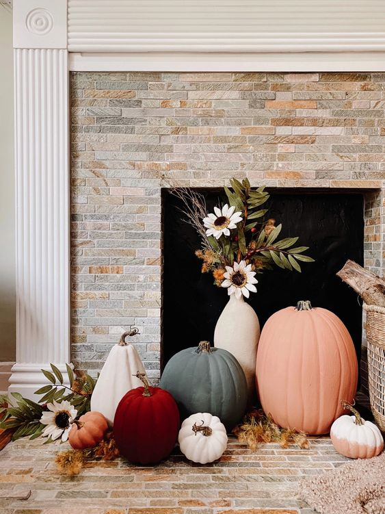 lovely fall fireplace styling with colorful pumpkins and a vase with faux blooms is an easy and lovely idea