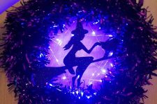 27 a purple Halloween wreath with purple lights and a witch on the broom silhouette is a fun and cool decoration
