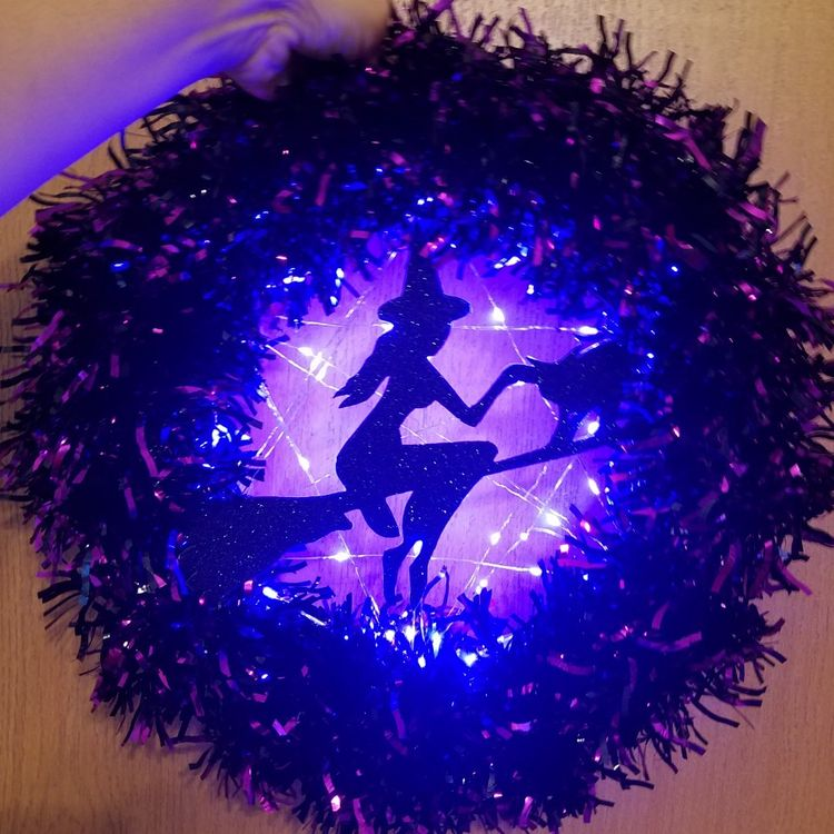 a purple Halloween wreath with purple lights and a witch on the broom silhouette is a fun and cool decoration