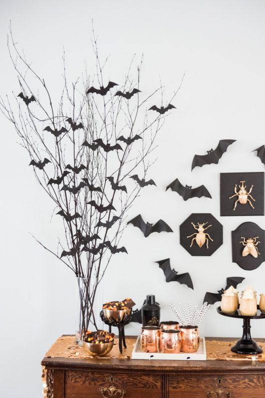 a sweets table with branches with black paper bats attached to them and to the wall, gilded bugs in frames