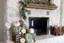 27 rustic fireplace styling with heirloom pumpkins and greenery in a crate, a wire basket with firewood and a greenery garland on the mantel