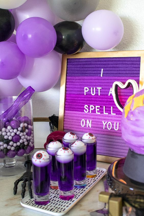 a purple Halloween sweets table with purple, black and lilac balloons, an ombre purple sign and various sweets is a cool idea