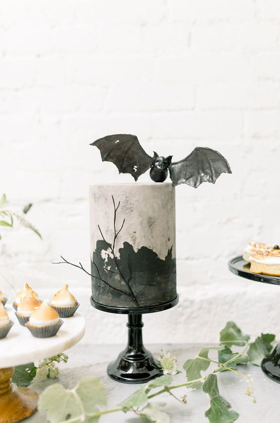 a stylish painted Halloween cake topped with a pretty black bat is a gorgeous solution to go for