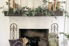 28 farmhouse fireplace styling with a crate with pumpkins and wheat, vintage churns, greenery and pillar candles on the mantel