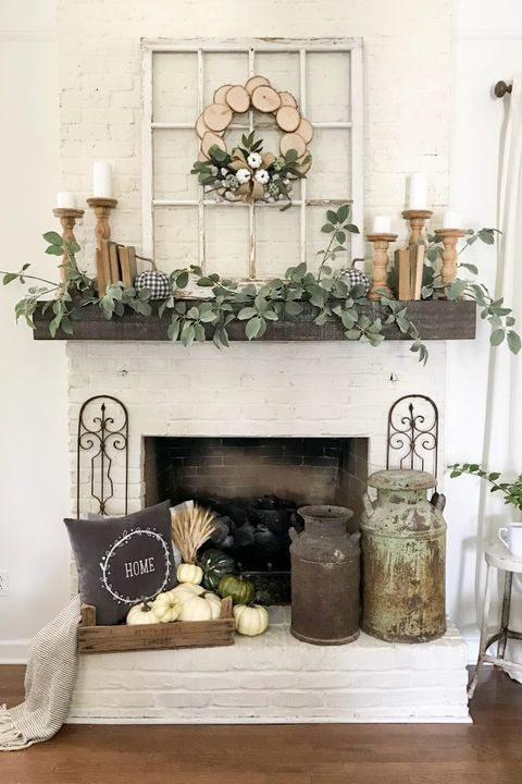 farmhouse fireplace styling with a crate with pumpkins and wheat, vintage churns, greenery and pillar candles on the mantel