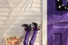 29 a purple door with a black frame wreath and a basket with apples with witch's legs in striped purple stockings
