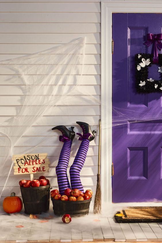 a purple door with a black frame wreath and a basket with apples with witch's legs in striped purple stockings