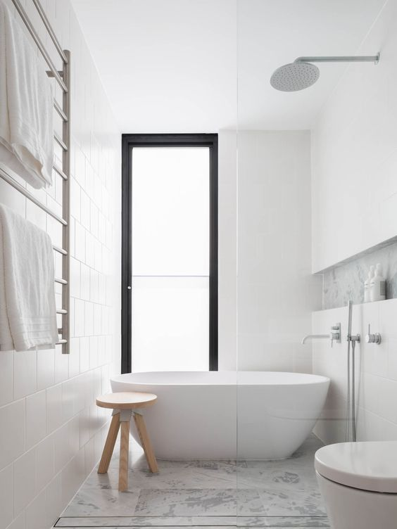 a neutral contemporary bathroom clad with white and marble tiles, with a floor to ceiling window done with frosted glass is a chic space