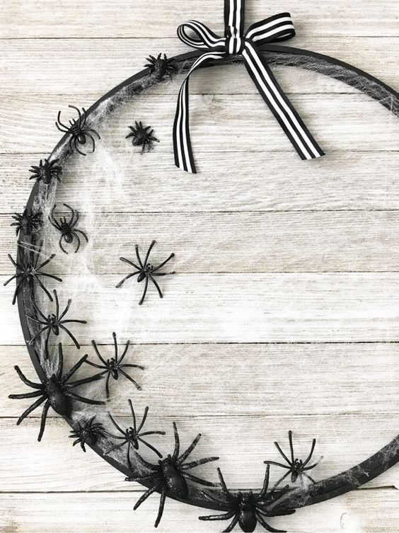an elegant Halloween wreath of a hoop, with spiderwebs, black spiders and a striped bow on top is a chic solution