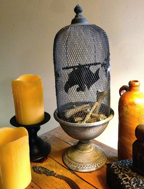 a lovely Halloween porp with a faux cage with a bat and lots of pillar candles is a stylish idea that you can easily DIY