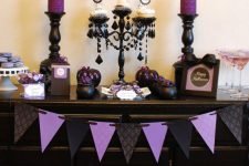 32 vintage black and purple Halloween decor with a paper bunting, purple glitter candles, black pumpkins and purple candies