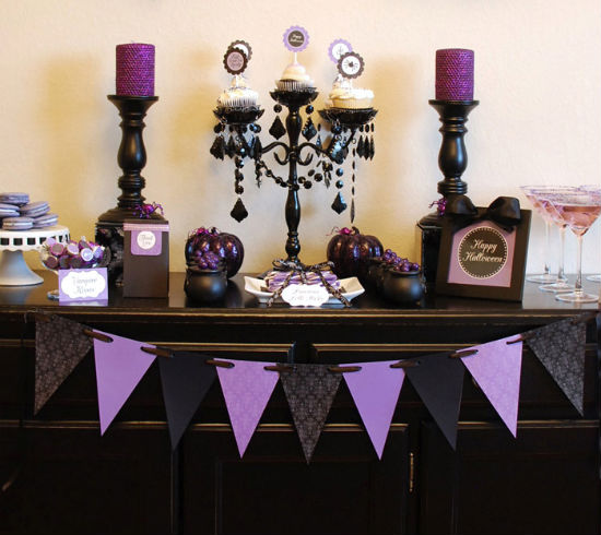 vintage black and purple Halloween decor with a paper bunting, purple glitter candles, black pumpkins and purple candies