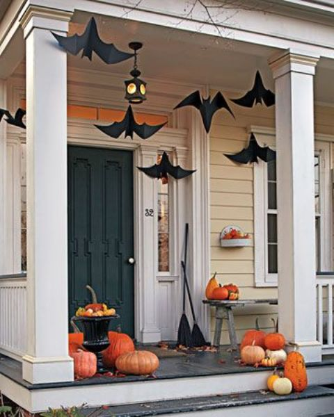 a Halloween porch with black paper bats hanging down, orange and neutral pumpkins on the floor, bench and steps is cool