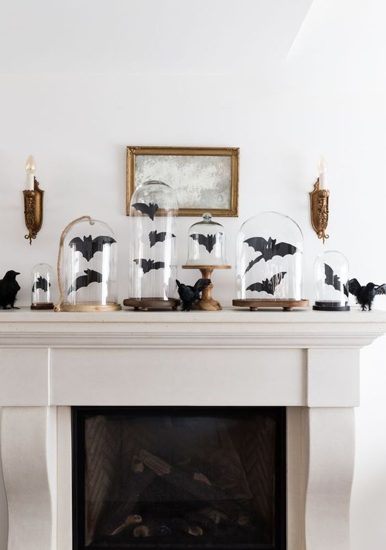 a Halloween mantel decorated with black paper bats in cloches and with blackbirds is a cool idea to go for