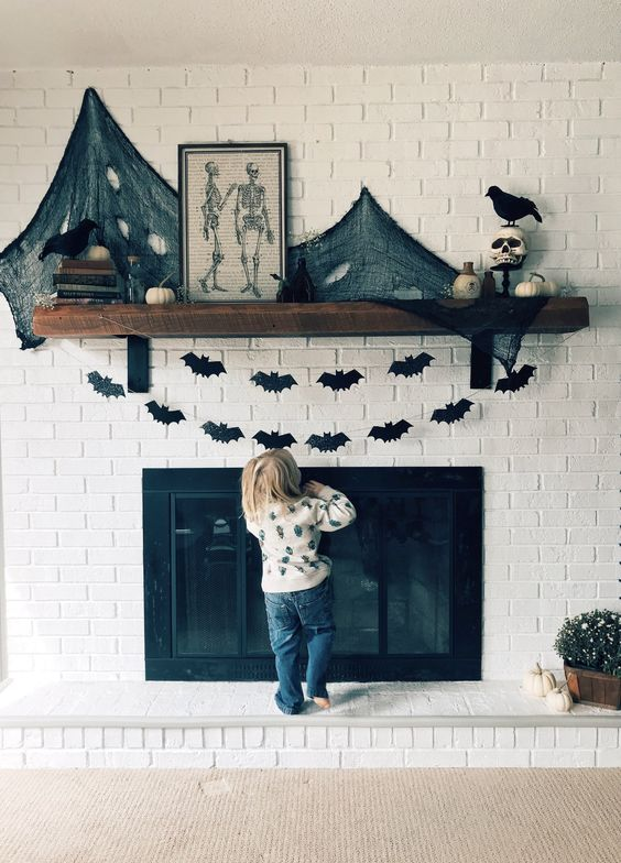 a Halloween mantel decorated with black paper bat buntings, black spider web and pumpkins plus skulls