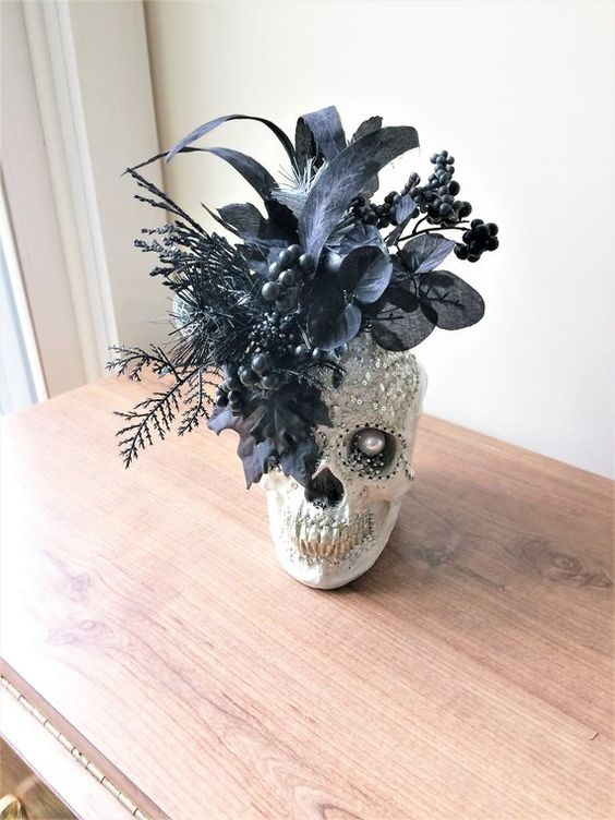 a Gothic Halloween decoration of an embellished skull with sequins and a pearl plus faux black blooms and leaves