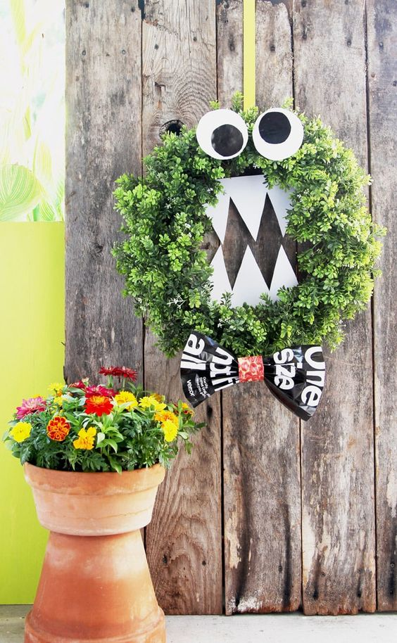 a Halloween monster wreath of faux greenery, eye sna dteeth of cardboard plus a bow is great for Tim Burton fans