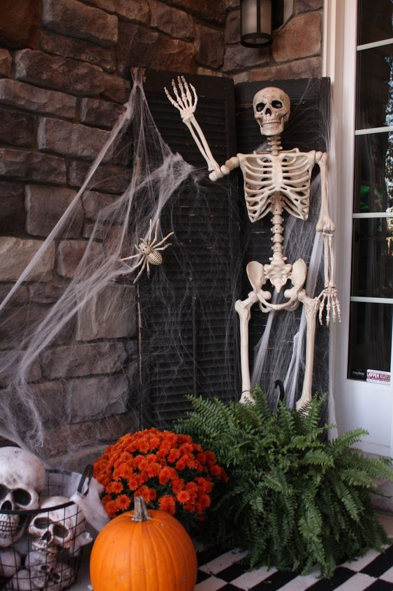 a Halloween porch styled with shutters, a skeleton, spiderweb, greenery and blooms, skulls and a bold pumpkin is a cool idea