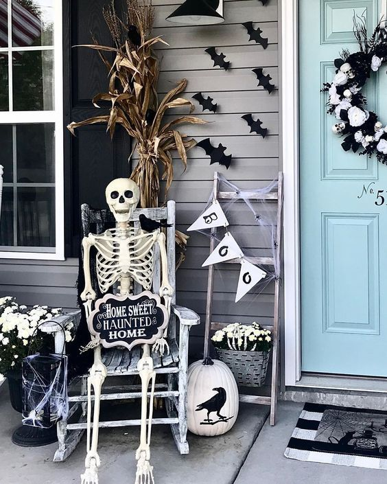 a Halloween porch with bats, a bunting, a skeleton rocking, cron husks and a skull wreath on the door is a cool idea