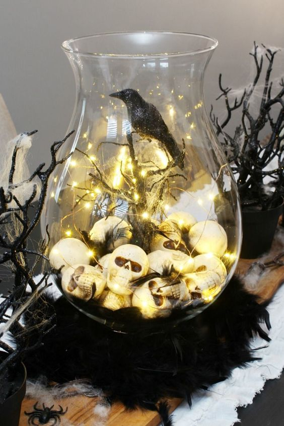 a Halloween terrarium of a large jar, skulls and lights, branches and spiderweb, a blackbird is a stylish idea for moody decor