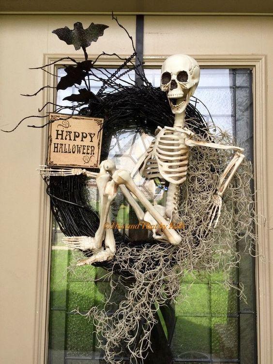 a Halloween wreath of black branches, hay, blackbirds, a sign and a skeleton is a very eye-catchy and creative idea