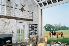 a barn living room with a tall attic ceiling is opened up to the outdoor fields with simple garage doors at once, and indoor becomes outdoor