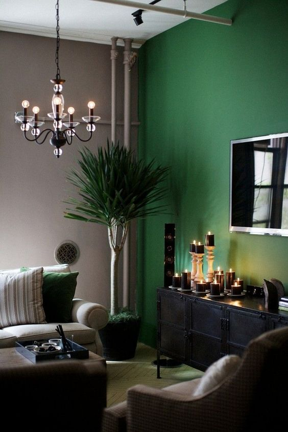 a beautiful and refined living room with grey walls and a green accent one, a chic black credenza, a neutral sofa, a unique chandelier and a potted tree