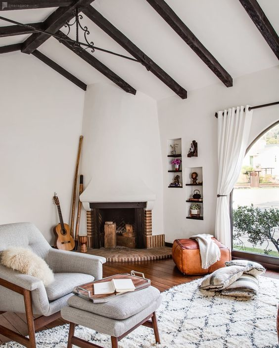 a beautiful and welcoming neutral living room with dark wooden beams, a large fireplace, a neutral chair with a footrest, built-in shelves and neutral textiles