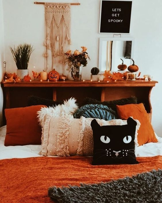 a beautiful boho fall to Halloween bedroom with a headboard with pumpkins, lights, leaves and jack-o-lanterns, a chalkboard sign and macrame plus a cat pillow