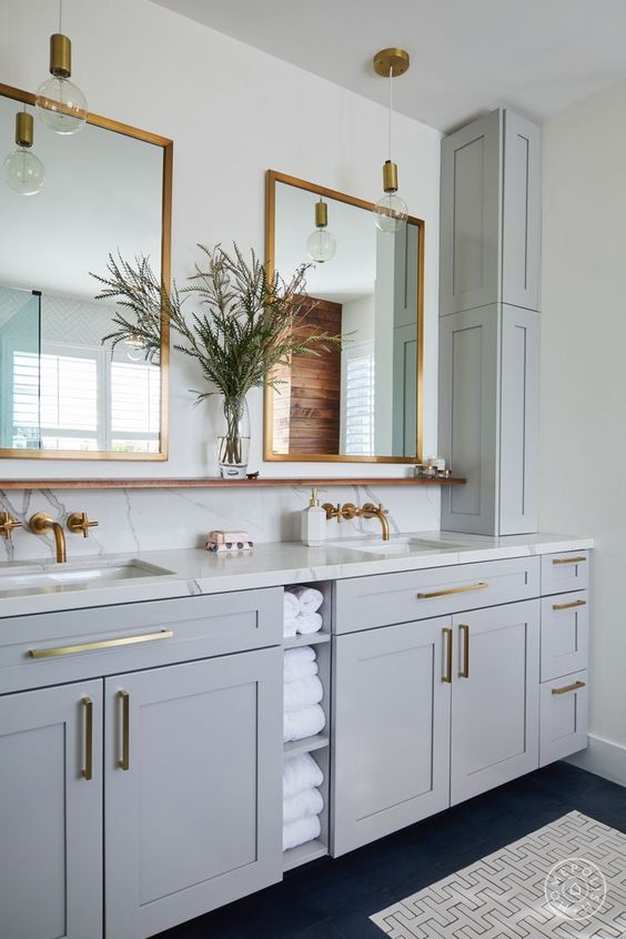 a beautiful dove grey bathroom with shaker style cabinets, white stone countertops and a backsplash, mirrors in brass frames, pendant bulbs, brass fixtures and handles