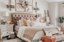 a beautiful farmhouse bedroom with a taupe upholstered bed, matching neutral nightstands, neutral bedding, an upholstered bench, orange touches, faux pumpkins and greenery