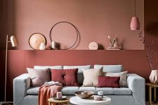 a beautiful living room with a pink and burgundy accent wall, a grey sofa, contrasting pillows, a pink pendant lamp, a trio of coffee tables and soem decor
