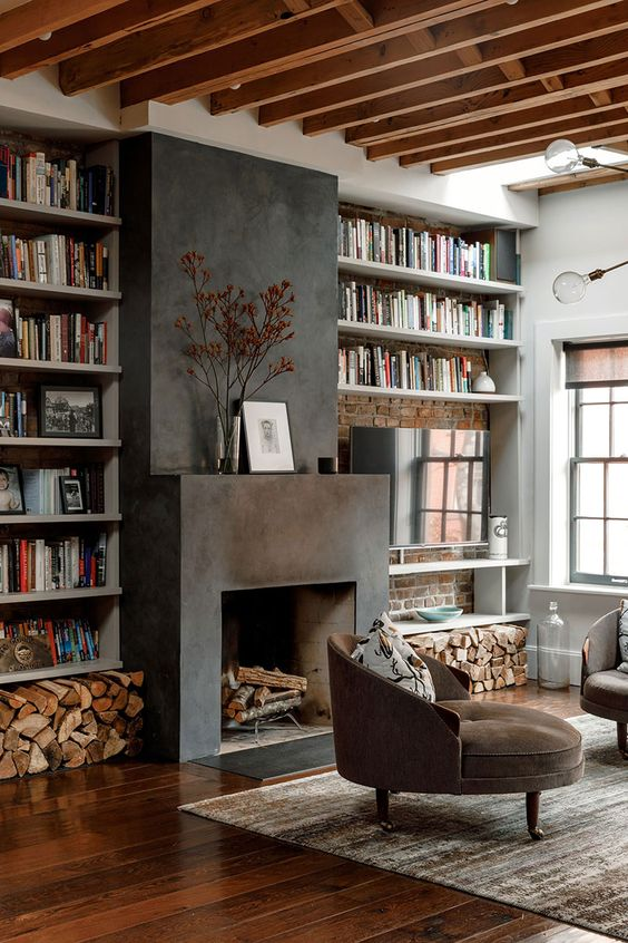 a beautiful living room with wooden beams, built-in shelves, a fireplace clad with cocnrete, firewood storage, brown chairs and a rug