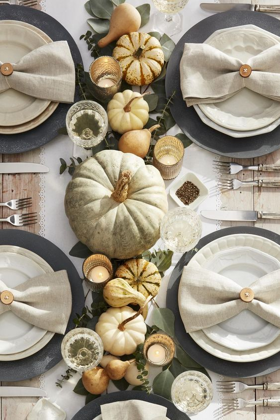 a beautiful rustic Thanksgiving tablescape with pumpkins, candles, greenery, black chargers and neutral napkins and a runner