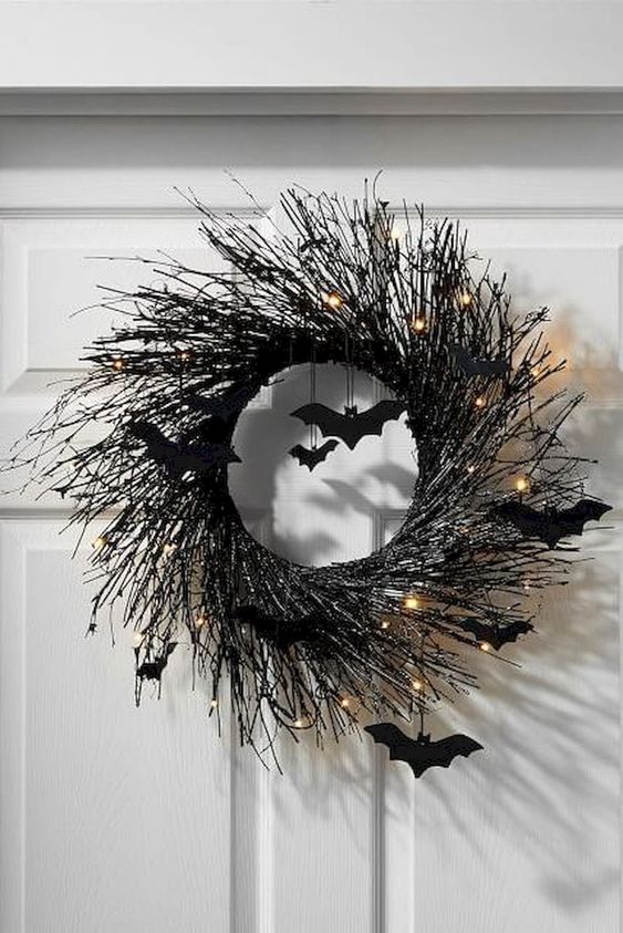 a black branch Halloween wreath with lights and black bats is a cool idea for front door decor and is elegant and stylish