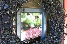a black vine Halloween wreath covered with snakes, spiders and insects of all kinds is a lovely idea to style your front door