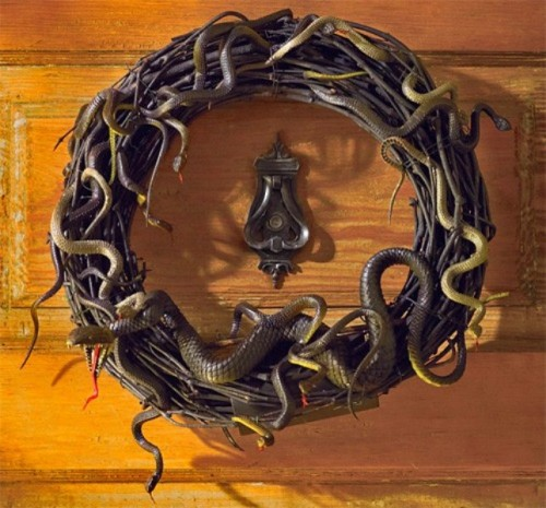 a black vine wreath with lots of snakes is a timeless front door decoration for Halloween
