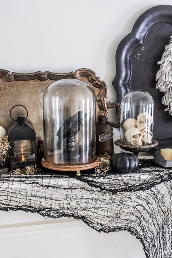 a blackbird on stand and some small skulls in cloches, a black candle lantern and hay for gloomy and moody Halloween decor