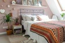 a boho attic bedroom with a dusty pink accent wall, a metal bed with neutral and bright boho bedding, nightstands, potted plants and a gallery wall